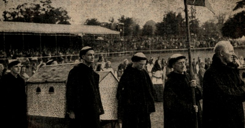 From the local newspaper, monks carrying a model of St Stephen's Church, with the grandstand in the background
